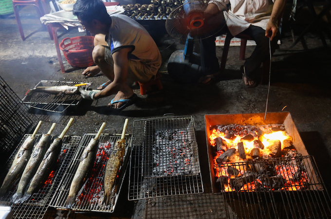 Dozens of grilled fish stalls have hired extra help with lighting charcoal, grilling the fish and preparing vegetable side dishes.