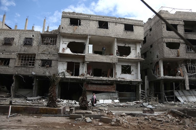 A Syrian man walks past destroyed buildings in the rebel-held town of Hamouria, in the besieged Eastern Ghouta region on the outskirts of the capital Damascus, on February 27, 2018. A humanitarian pause announced by Russia in Syrias deadly bombardment of Eastern Ghouta struggled to take hold, with fresh violence erupting and no sign of aid deliveries or residents leaving the besieged enclave.