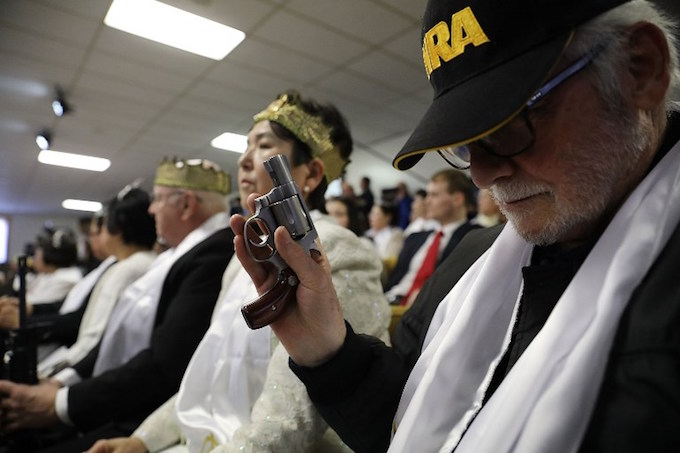 A man holds a pistol during a ceremony at the World Peace and Unification Sanctuary in Newfoundland, Pennsylvania on February 28, 2018