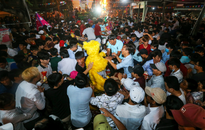 Locals in Tam Vu Town of Long An Province jump on each other to get at least one piece from the offerings at their towns temple on Saturday night, the final day of a three-day festival on the 14th, 15th, 16th of the first lunar month, as they believe that what they get will bring them luck for a new year.