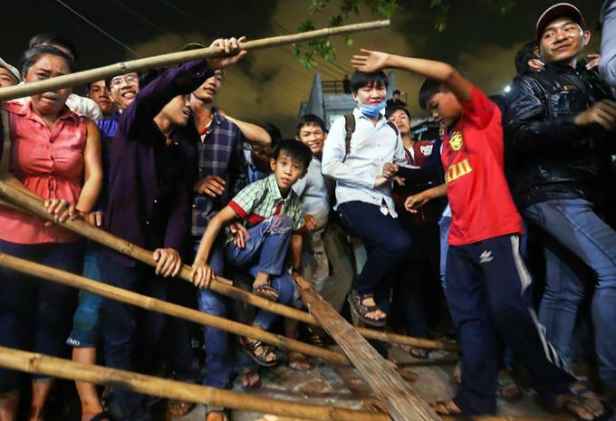 As soon as the Gods effigy is burned down, the crowd immediately trample down the makeshift fence that is set up temporarily for the festival to jump into the temples yard for the offerings. Trampling the fence is not a spontaneous or unthoughtful act of local people but a tradition of this festival, explains Nguyen Van Bach, 68.
