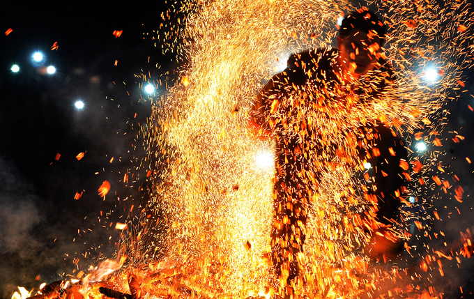 A fire dancers jumps around on the burning logs while grabbing and throwing red-hot coals into the air with his hands.