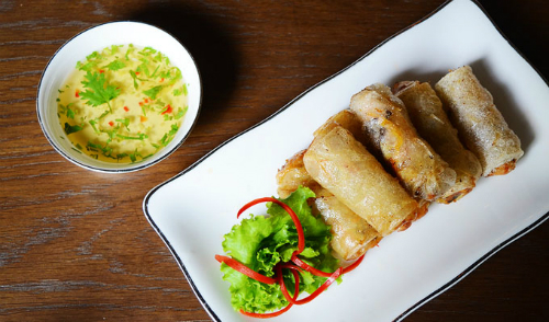 Spring roll is made by rolling lean minced pork or crab, sliced mushroom, glass noodle, carrots, eggs and spring onion in rice paper. The dish is very all over Vietnam with many variations. The deep fried rolls are eaten by dipping in fish sauce mixed with water, sugar, garlic, pepper and vinegar.