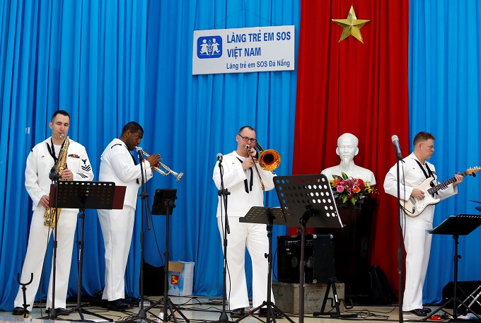 Members of U.S. Seventh Fleet Band perform as a statue of late Vietnamese revolutionary leader Ho Chi Minh is seen in the background, as part of the U.S aircraft carrier USS Carl Vinson to Vietnam, at the Da Nang SOS Childrens Village in Danang, Vietnam March 6, 2018. Photo by Reuters/Kham
