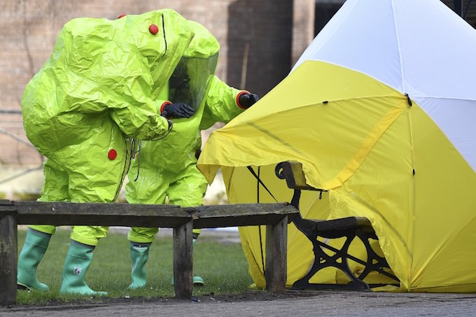 Members of the emergency services in green biohazard suits afix the tent over the bench where a man and a woman were found on March 4 in critical condition at The Maltings shopping centre in Salisbury, southern England, on March 8, 2018 after the tent became detached. British detectives on March 8 scrambled to find the source of the nerve agent used in the brazen and reckless attempted murder of a Russian former double-agent and his daughter. Sergei Skripal, 66, who moved to Britain in a 2010 spy swap, is unconscious in a critical but stable condition in hospital along with his daughter Yulia after they collapsed on a bench outside a shopping centre on Sunday.