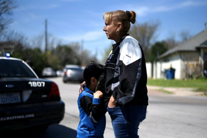 Isaac Machado hides behind his hat against his mother Delores just outside the scene of an explosion. Police investigators are at the home where a 17-year-old boy was killed and a woman injured in a package bomb explosion in Austin, Texas, U.S., March 12, 2018. Photo by Reuters/Sergio Flores