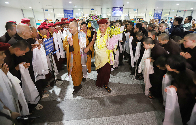 Crowd of Buddhists gather in the airport to welcome the Buddhist leader and his Sangha.