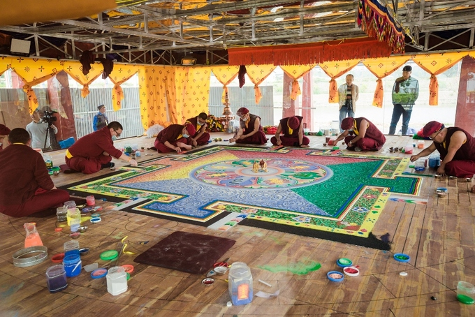 In the mandala stupas pavilion, protected by toughened glass walls, twenty lamas (Tibetan Buddhist monks) from the Himalayas are working day and night to finish this mandala of Bodhisattva Guanyin.