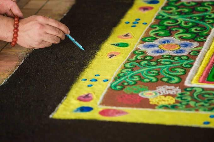To color the mandalas backgrounds, the lamas have to slowly and carefully scatter precious gemstone powders by hand to evenly fill in the spaces.