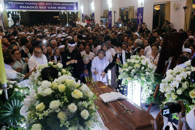 Thousands of Christians gather on Thursdays night to pay tribute to Archbishop Paul Bui Van Doc, who has served as the Archbishop of Ho Chi Minh City since 2014, as his coffin arrives at the Archbishops Palace in Ho Chi Minh Citys District 3.