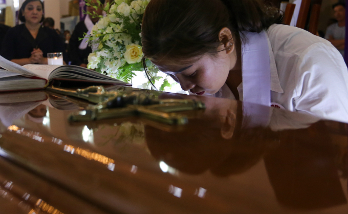 A woman kisses the coffin.