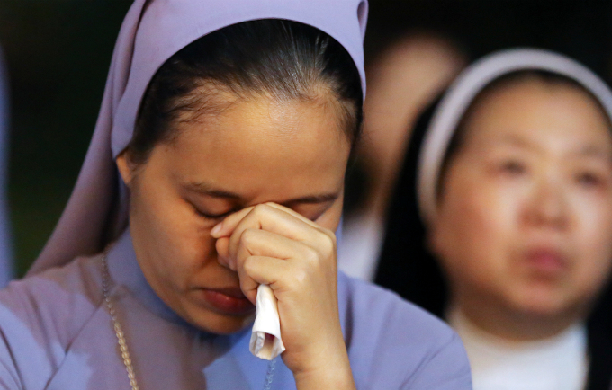 A nun keeps her head down while praying. Many Christians stay up all night with her to pray for the soul of Archbishop Doc.