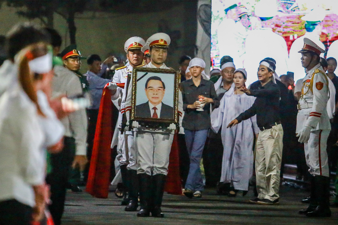 The funeral team carries Khais picture as his family members leave their house at 7 p.m., to transport his coffin to the Independence Palace in District 1.
