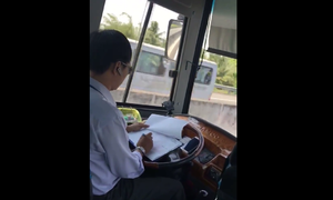 Video captures Vietnamese bus driver busy doing paperwork at the wheel