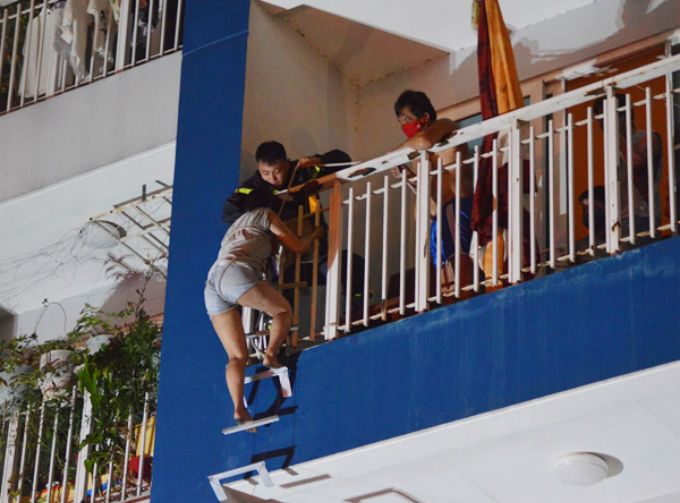 A woman was helped climb down a rope ladder. Photo by VnExpress