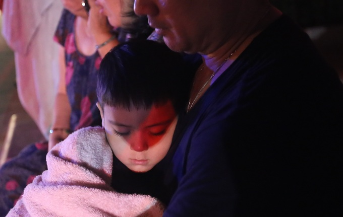 Pictured: A child dozes off in his mothers arms after the fire.