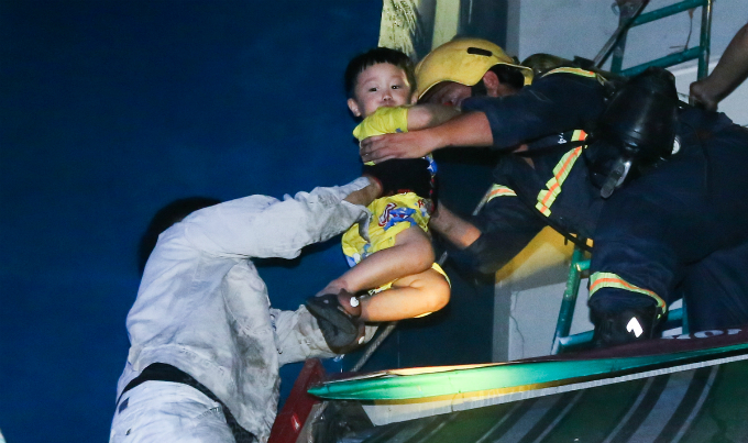 A woman and a little boy are taken out of the building on a fire truck lift. Photo by Quynh Tran