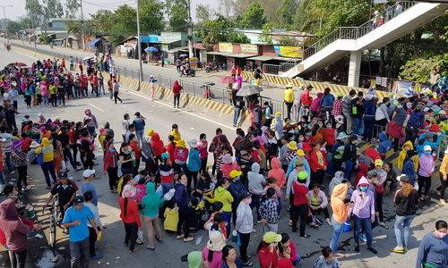 Thousands of Vietnamese workers take to highway to protest wage cuts