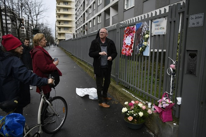 A man places a picture of Mireille Knoll and a message announcing a Marche Blanche condemning the alleged antisemitic motive for of her killing, placed on the fence surrounding her building in Paris on March 27, 2018, after she was found dead in her apartment on March 23 by firefighters called to extinguish a blaze. Photo by AFP/Lionel Bonaventure