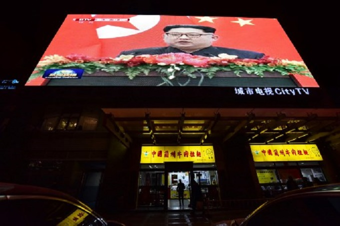 News video footage of North Korean leader Kim Jong Un during his meeting with Chinas President Xi Jinping is seen on a large screen above a restaurant in Beijing on March 28, 2018. Photo by AFP/Greg Baker