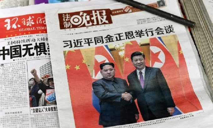 North Korea's Kim shows unity with China's Xi in first foreign trip
