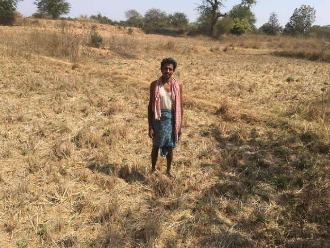 Kumar Gwal poses for a photo on his dry farmland in the drought-hit Kharkhara village in the eastern state of Odisha, India, Feb 28, 2018. Photo by Thomson Reuters Foundation/Roli Srivastava