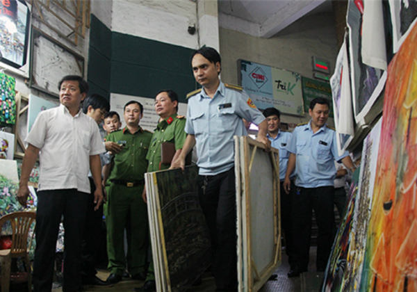 Inspectors remove paintings that were obstructing a corridor in an apartment building on Ly Tu Trong Street. Photo by VnExpress/Duy Tran.