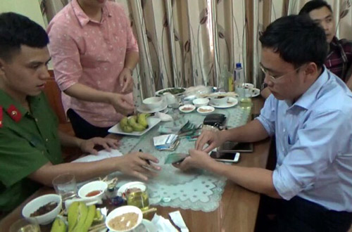 Le Duy Phong (R) works with a policeman after being caught taking money from a businessman in Yen Bai Province in order to ingore his business operation in June 2017.