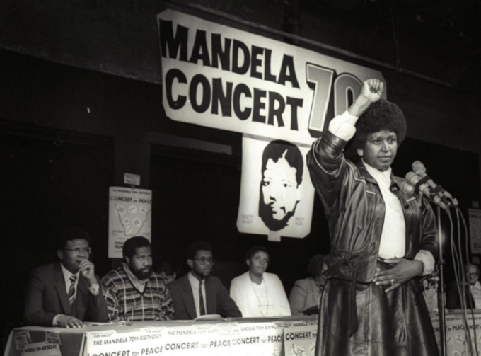 Winnie Mandela raises her fist in black power salute afte announcing that a massive pop concert will be held to mark the 70th birthday of her husband, jailed black nationalist leader Nelson Mandela on July 17, 1988. Photo by Reuters/Wendy Schwegmann