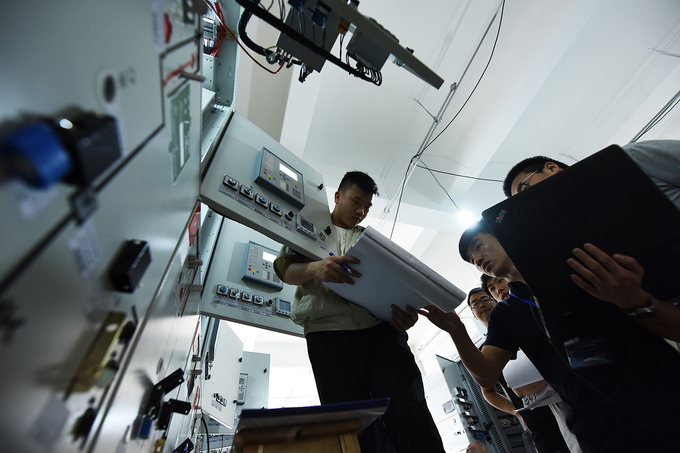 Electricians double-check electric panels.Chinese engineers install and double-check equipment in electric booths. Most equipment were imported from China.