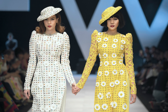 Pop singer Ho Ngoc Ha (L) and model Thanh Hang walk together as vedettes  in the Coco La Bien Aimée collection by Vietnamese designer Cong Tri  that opens the Vietnam International Fashion Week Spring Summer 2018  (VIFW 2018) in Ho Chi Minh City between April 19 and 22. Their outfits  are Vietnams traditional dress ao dai with a Western touch.