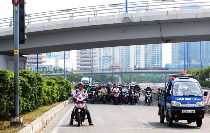 Motorbike drivers hide under a  bridge awat from the red light as afternoon temperatures reach 37-39 degrees Celsius, or 98.6 -102 degrees Fahrenheit.