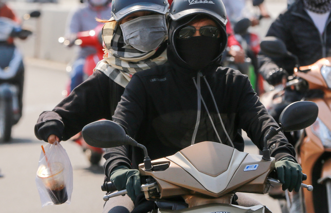 Motorbike drivers wrap themselves up from the sun.