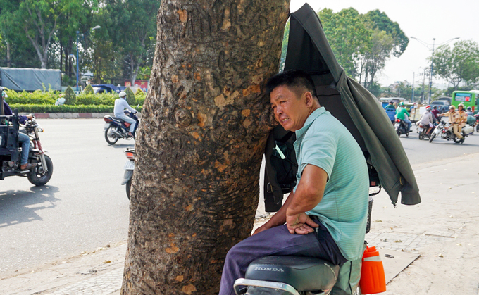Phan Tan, a xe om motorbike taxi driver, uses a  jacket to shield him from the sun while waiting for passengers on Truong  Chinh Street in Tan Binh District.