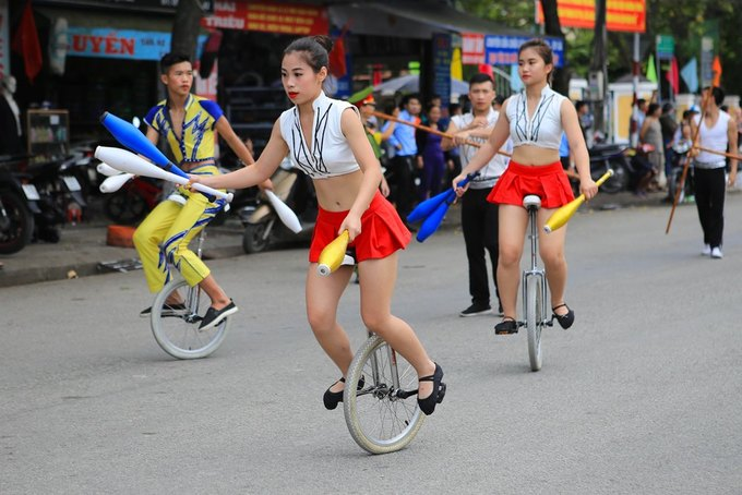The Vietnamese circus team juggle on unicycles.
