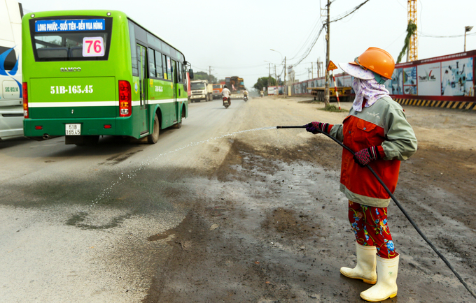 A female worker covers up her face to spray water onto the road to cool down the temperatures.
