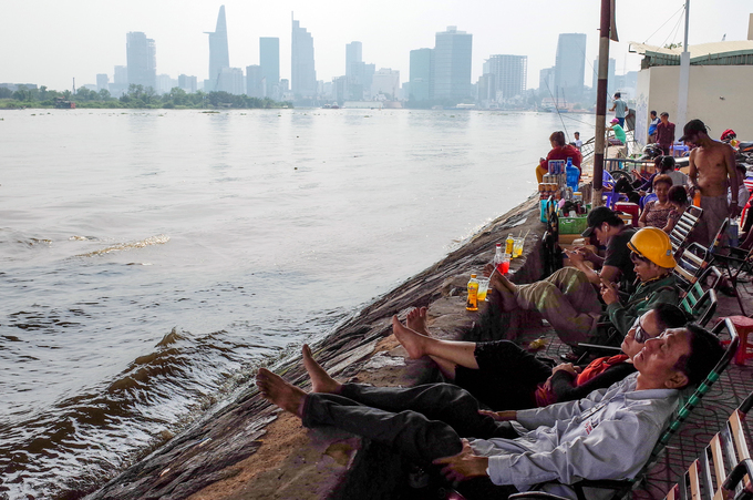Many residents flock to the bank of Saigon River to rest and enjoy a cool atmosphere there.