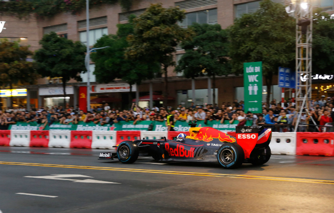 A crowd is seen waiting for the F1 racing car. The car has been lifted to adapt to the street condition in Vietnam.