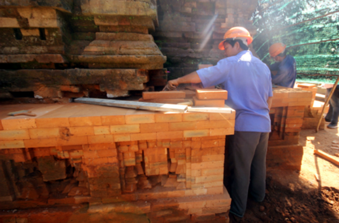 A worker rebuilds the foundation of a temple with new bricks. Photo by VnExpress/Dac Thanh
