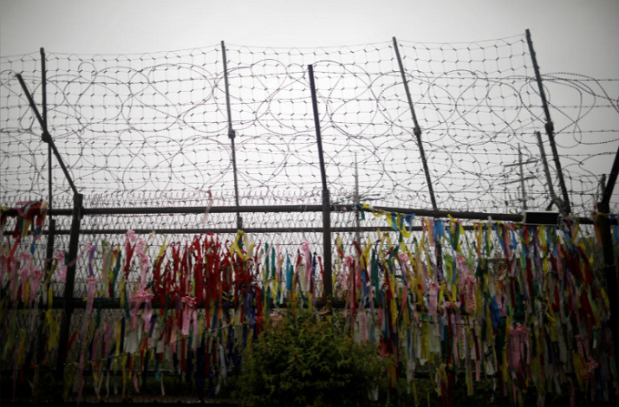 A barbed wire fence is decorated with ribbons bearing messages wishing for unification of the two Koreas near the demilitarized zone separating the two Koreas, in Paju, South Korea, May 16, 2018. Photo by Reuters/Kim Hong-Ji
