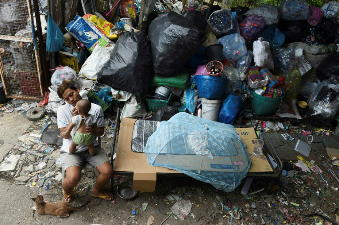 This picture taken on June 1, 2018 shows Bangorn Kokiam sorting out collected plastic water bottles and other recyclable scraps at her junk shop in Bangkok. Photo by AFP/Romeo Gacadon