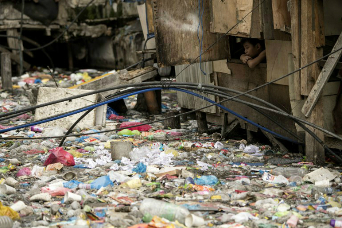 This photo taken on May 12, 2018 shows a boy looking out from a window of a house beside a garbage-filled creek in Manila. Photo by AFP/Noel Celis