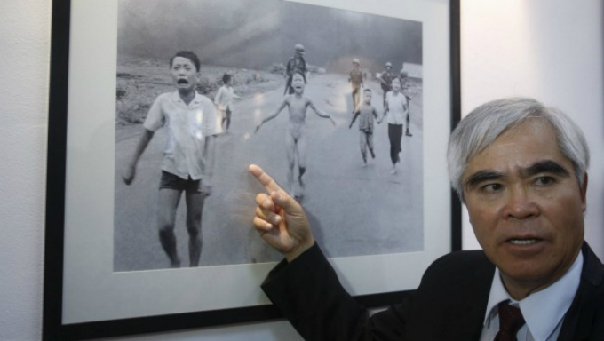 Photographer Nick Ut speaks to the media next to his photo Napalm Girl. Officially known as The Terror of War, the black and white photo shows a  terrified girl, Phan Thi Kim Phuc, running naked and screaming after  being burned in a napalm attack by the U.S. on June 8, 1972. Photo by Reuters