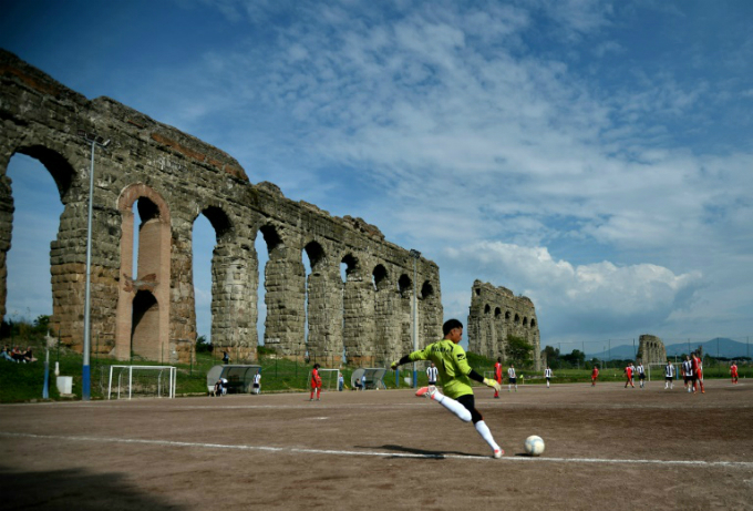 Players compete at the Campo Gerini football ground nestled inder one of Romes ancient acqueducts. Photo by AFP