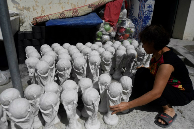 A worker arranging plaster models of the football World Cup trophy to dry.