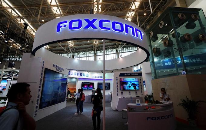 Visitors are seen at a Foxconn booth at the World Intelligence Congress in Tianjin, China May 19, 2018. Photo by Reuters/Stringer