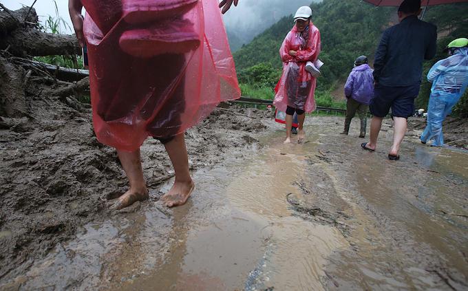 Locals carrying shoes to get pass the muddy road.