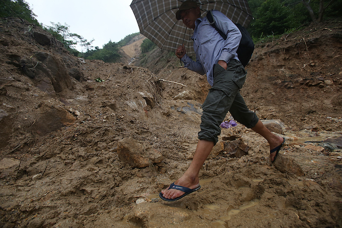 [Caption] A man rushes to get pass the landslide despite the heavy rain.