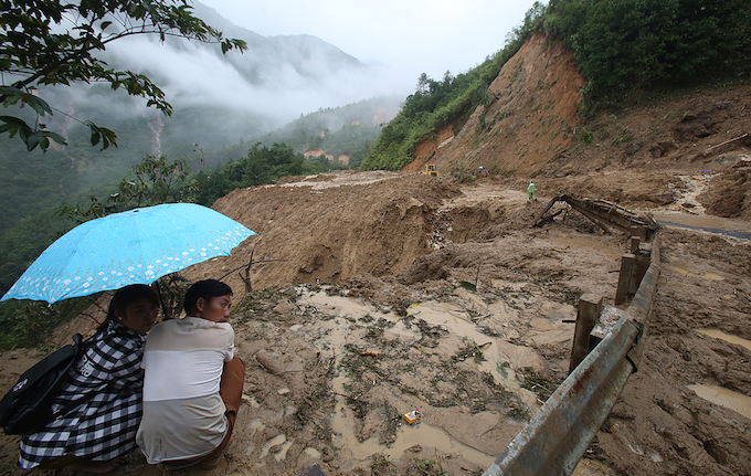 A Hmong couple wait for the excavator to clear the road. But as soon as the road was cleared, another mass of soil fell right at the same spot.