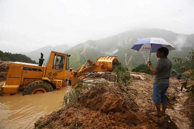 [Caption] Cranes and bulldozers have been working non-stop at the landslide. But strong water from the mountain keep flowing down and obstruct the work.